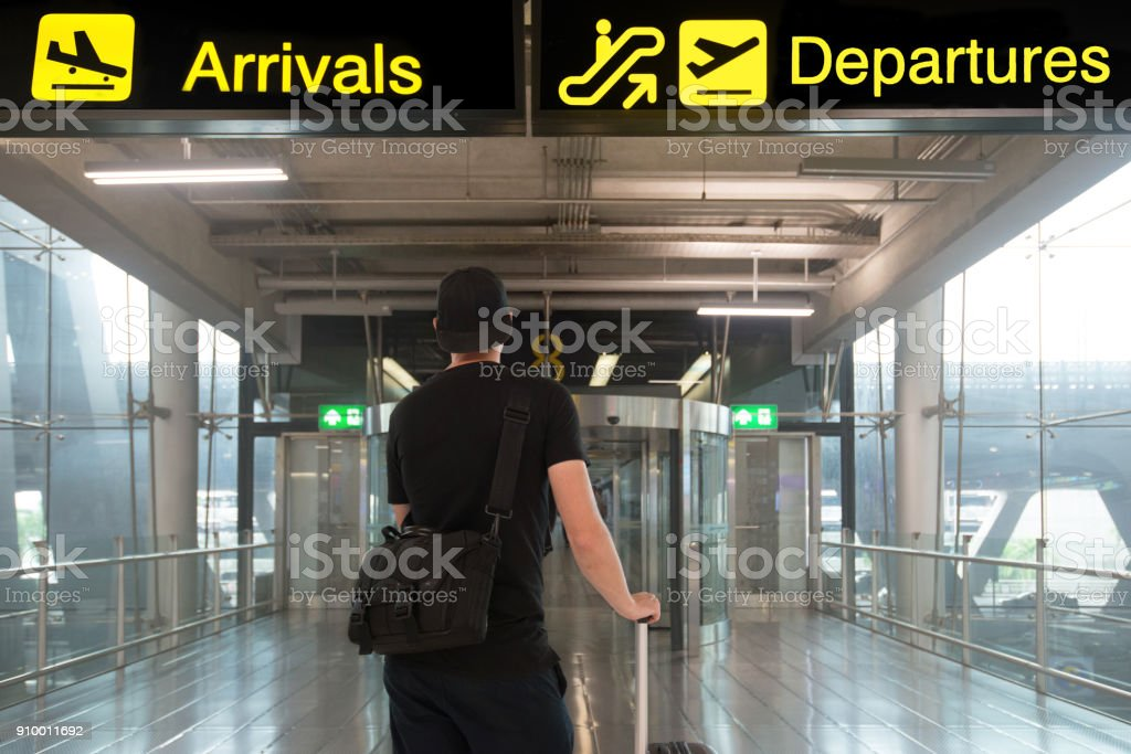 Man In Travel With Suitcase In Front Of Billboards Of Departures And Arrival In Airport Stock Photo Download Image Now Istock