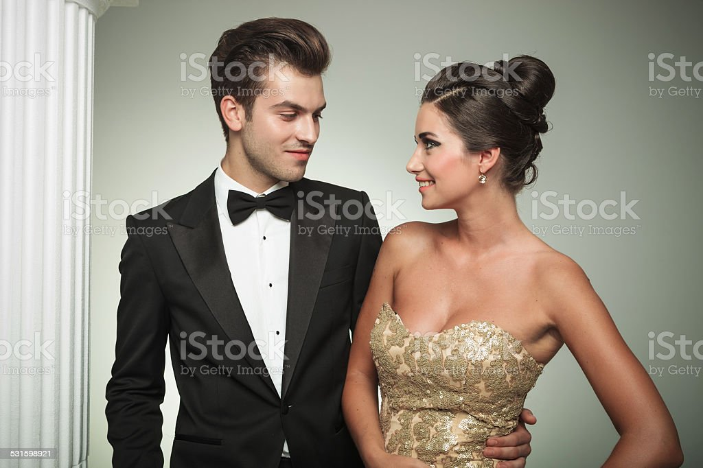 man in tuxedo embracing his woman and smiles stock photo