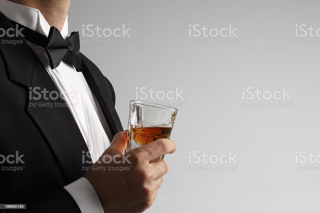 Man in tuxedo holding whiskey shot glass against gray background royalty-free stock photo
