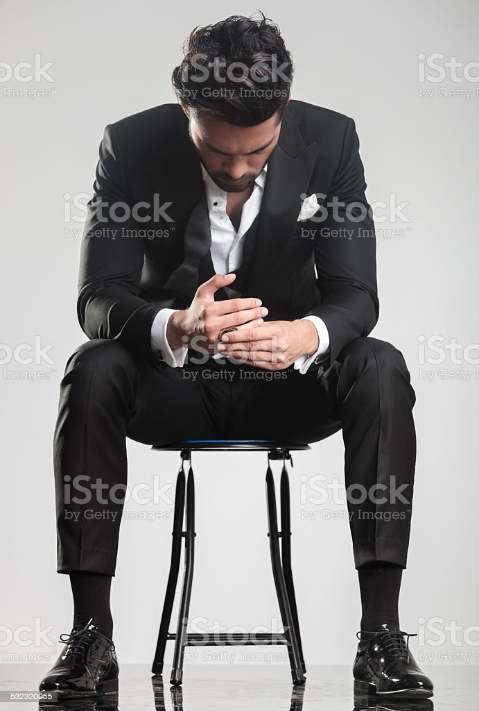 man in tuxedo looking down while sitting on a stool, stock photo