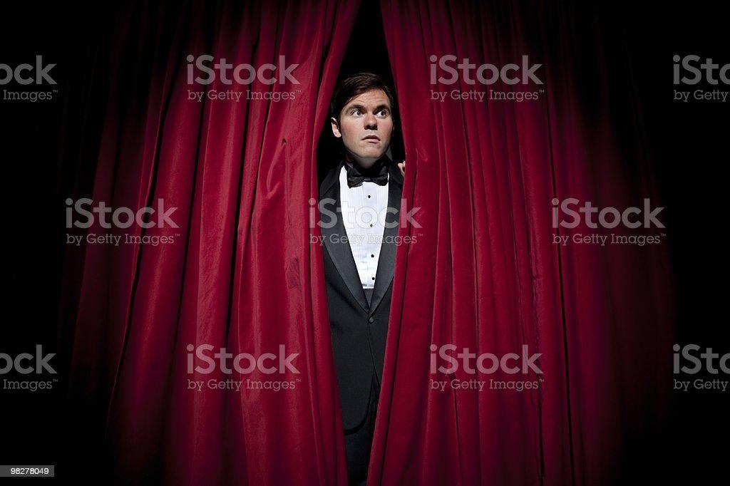 Man in tuxedo peeking through curtain royalty-free stock photo