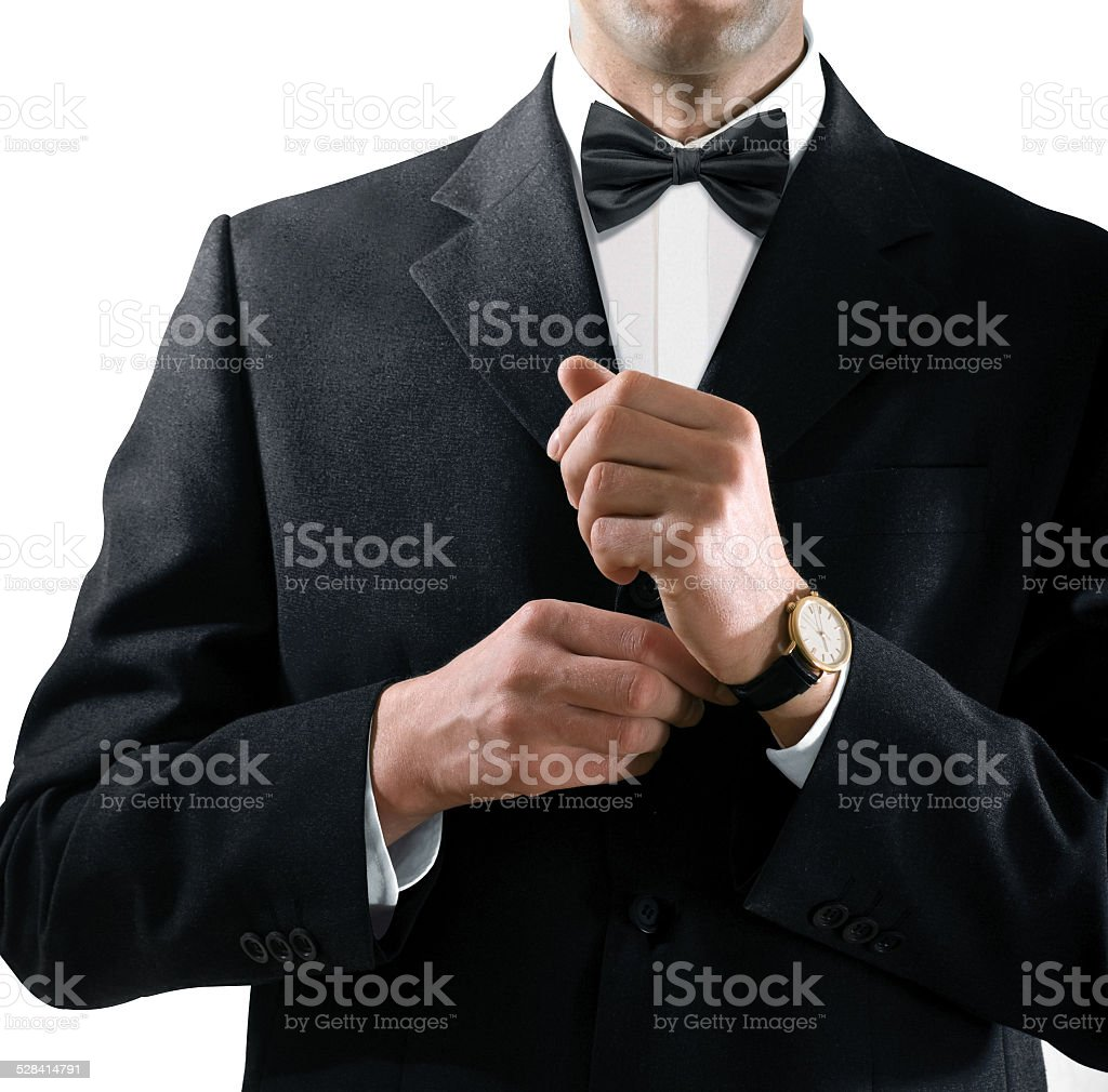 man in tuxedo puts on watch stock photo