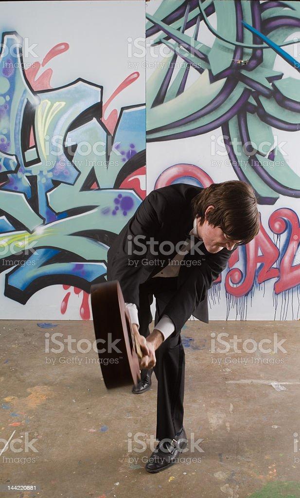 Man in Tuxedo Smashing a Ukelele on Ground stock photo