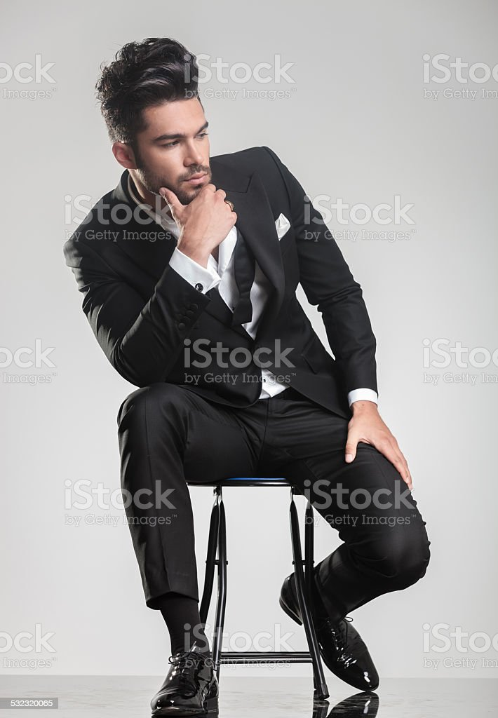 man in tuxedo thinking, holding one hand to his chin. stock photo