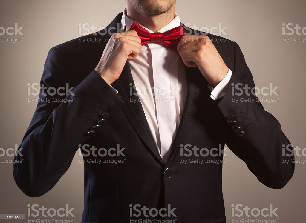 Man in tuxedo tying bow tie stock photo