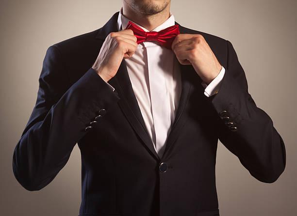 Man in tuxedo tying bow tie stock photo