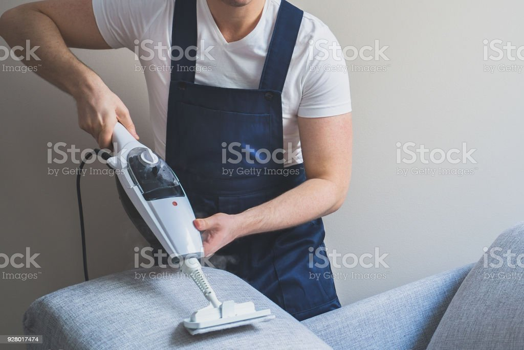 Man in uniform cleaning sofa with dry steam cleaner. Place for text. Man in uniform cleaning sofa with dry steam cleaner. Place for text. Adult Stock Photo