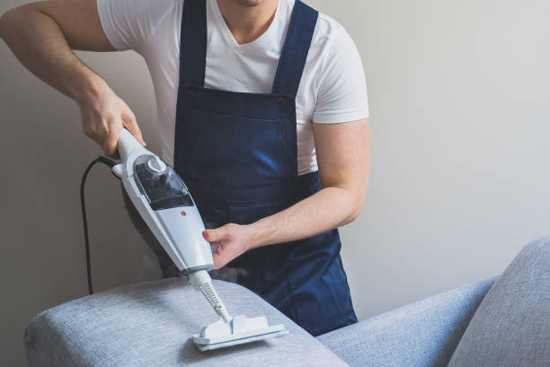 Man in uniform cleaning sofa with dry steam cleaner. Place for text. stock photo