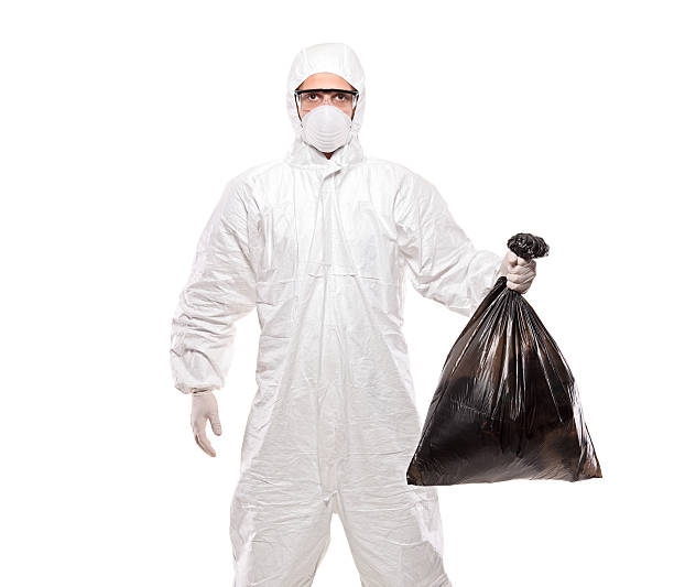 Man in uniform holding a black garbage bag stock photo