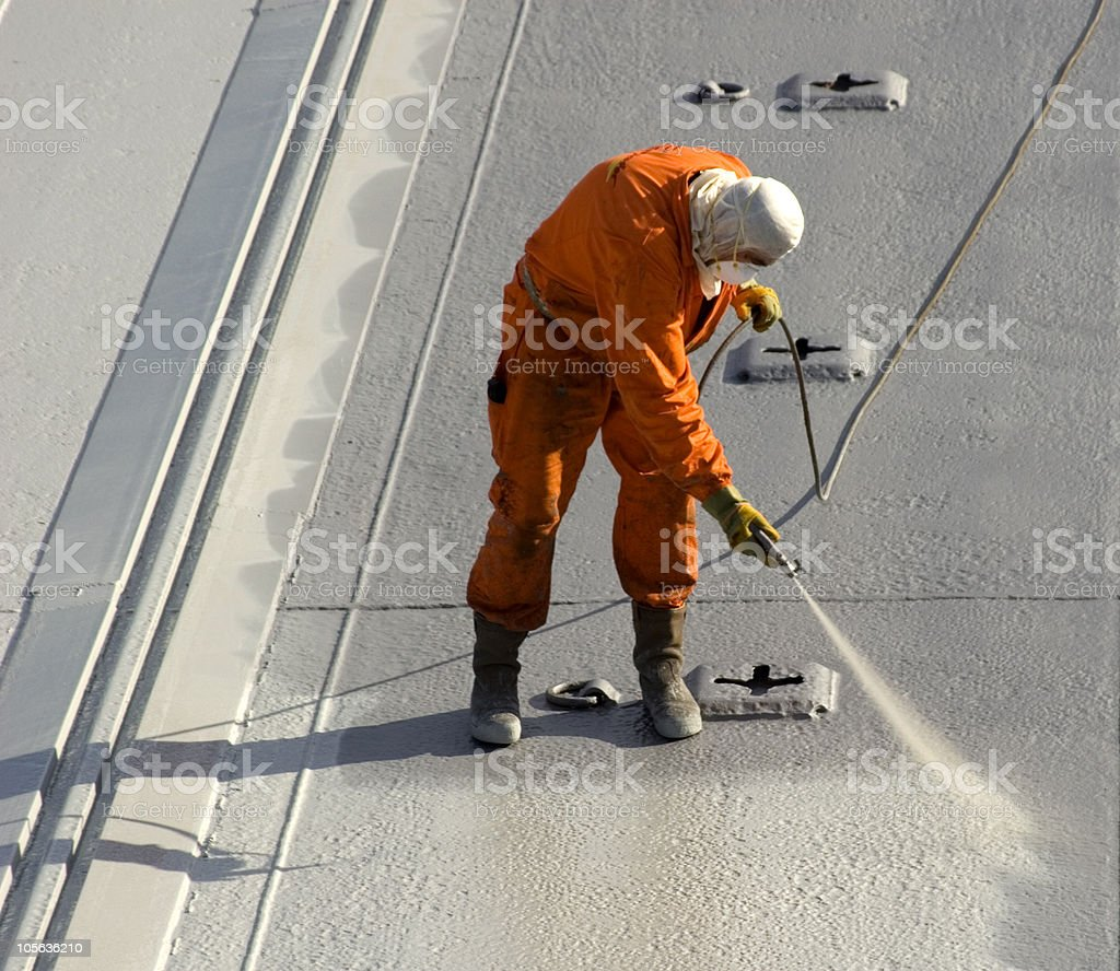 A man in uniform spray painting stock photo