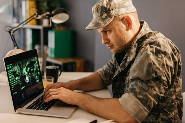 Man in uniform working on the laptop stock photo