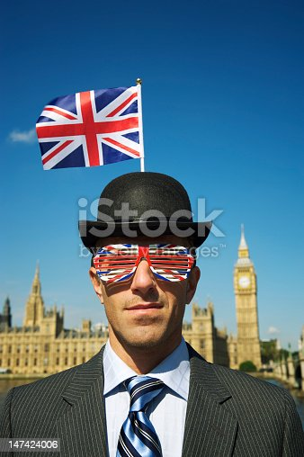 Man in Union Jack Bowler hat stands in front of Westminster Palace on a blue sky day