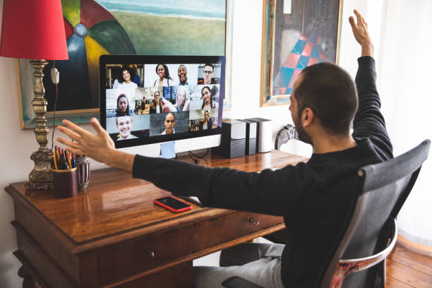 man in video call with friends and relatives in front of computer - family gatherings stock pictures, royalty-free photos & images