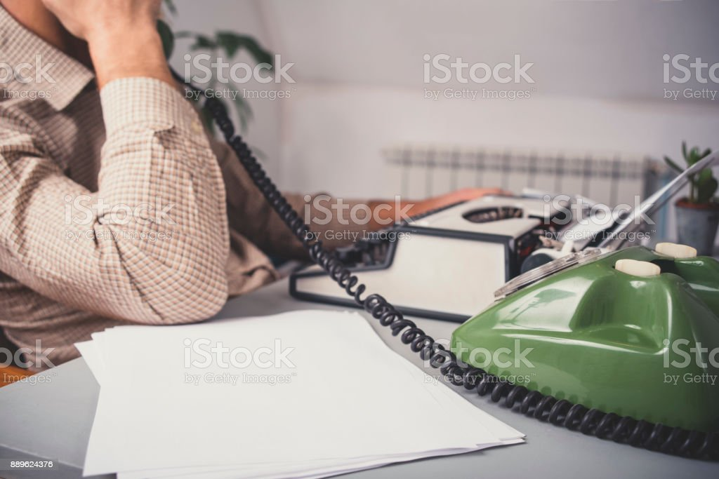 Man in vintage office uses green rotary telephone in front of...