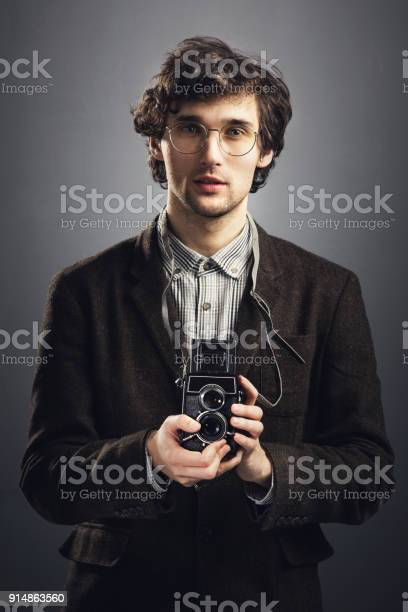 Man in vintage suit with retro camera.