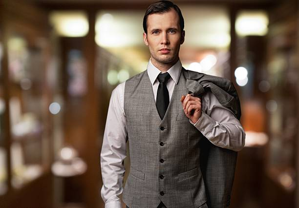 Man in waistcoat with jacket over his shoulder stock photo