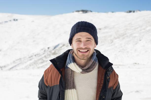 mann in warme kleidung stehend auf verschneiten landschaft - gute winterjacken stock-fotos und bilder