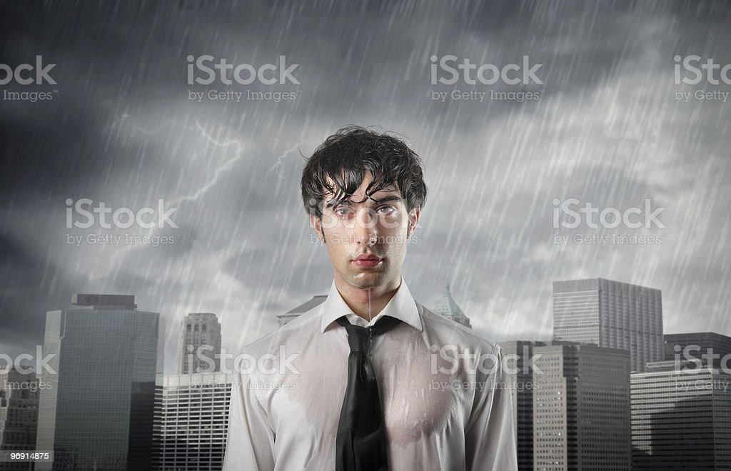 Man in wet shirt in front of city buildings being rained on stock photo