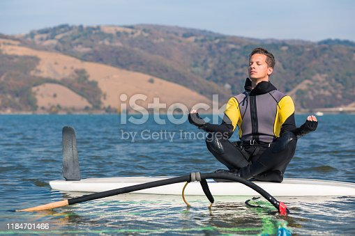 istock Man in wetsuit sitting on surfing board in lotus position and doing meditation zen exercise. Windsurfing and life balance concept. 1184701466