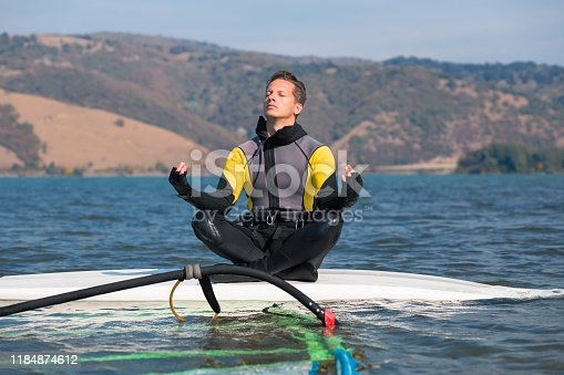 istock Man in wetsuit sitting on surfing board in lotus position and doing meditation zen exercise. Windsurfing and life balance concept. 1184874612