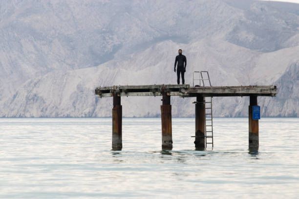 Man in wetsuit standing on sea platform stock photo