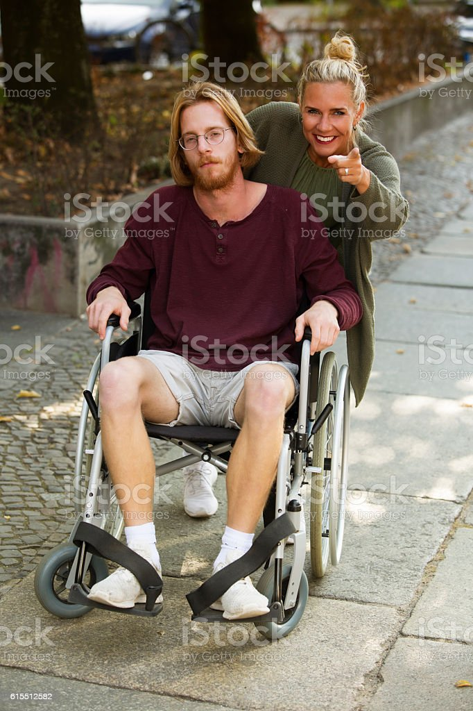 man in wheelchair and woman showing him something stock photo