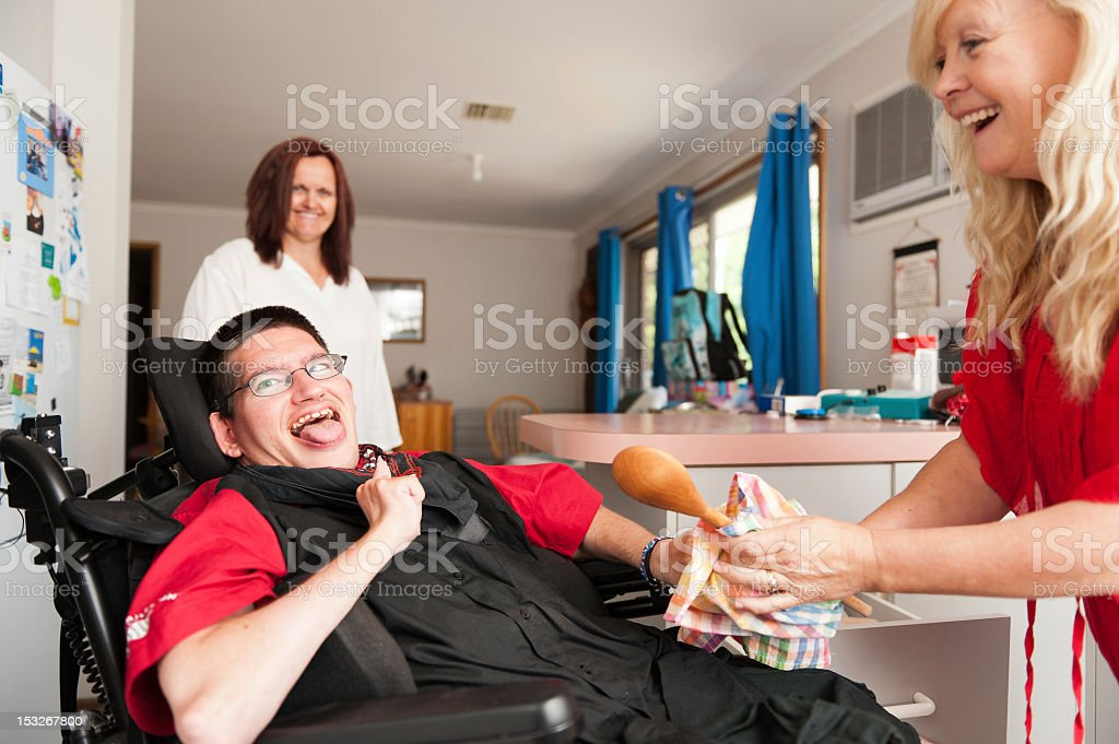 Man in wheelchair being assisted to wipe dry a spoon stock photo