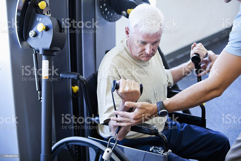 Man in wheelchair doing physical therapy exercises stock photo