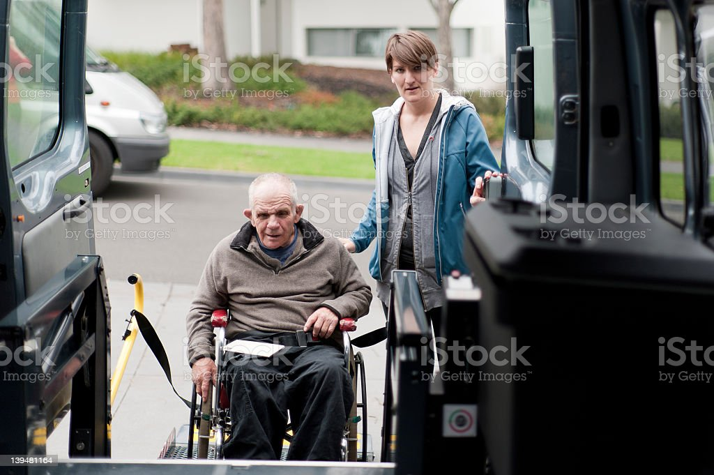 Man in wheelchair entering a modified van stock photo