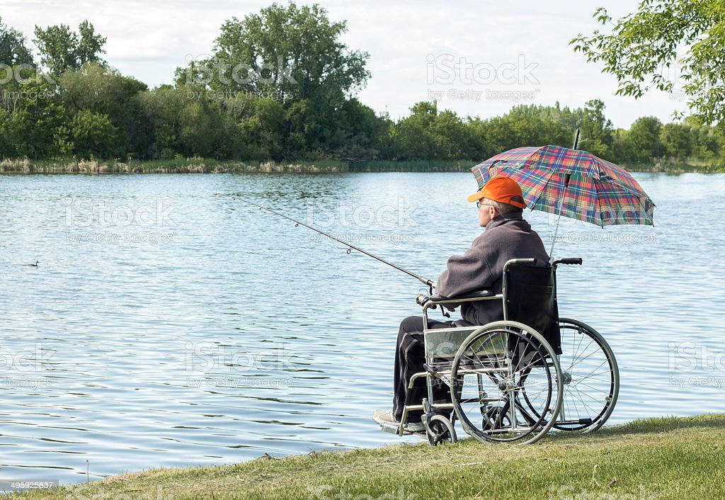 man in wheelchair fishing stock photo