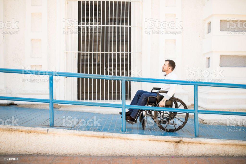 Mann im Rollstuhl eine Rampe hinauf – Foto