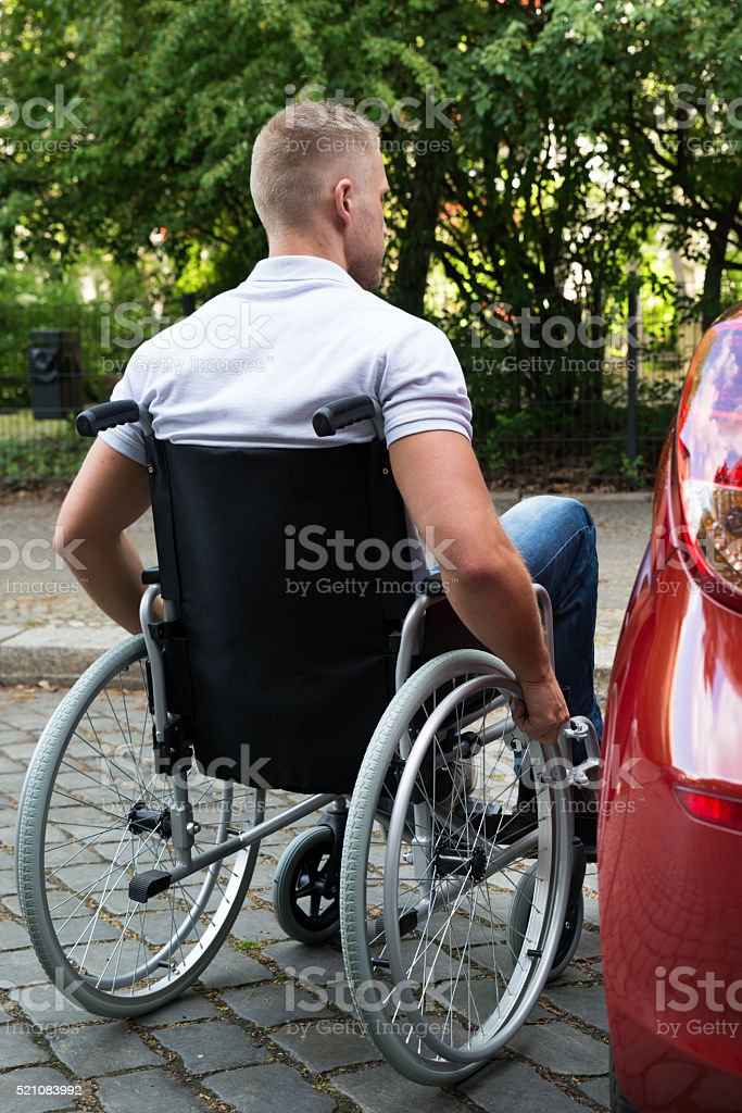 Man In Wheelchair Next To His Car stock photo