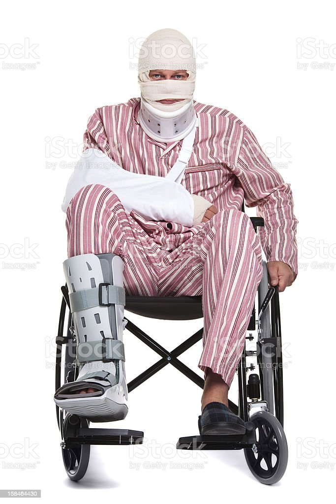 Man in wheelchair with broken leg and bandaged head and arm stock photo