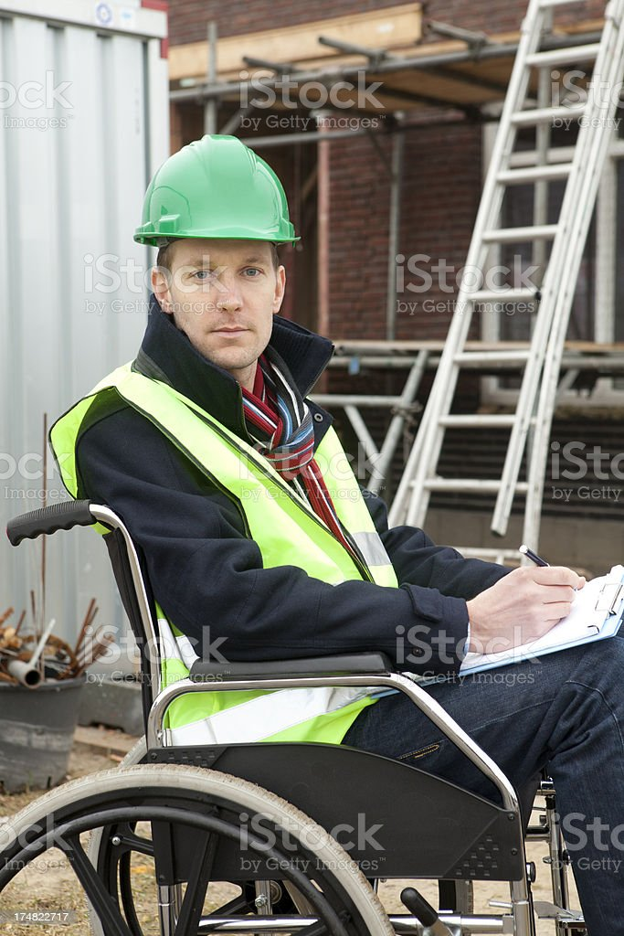 Man in wheelchair working as construction worker royalty-free stock photo