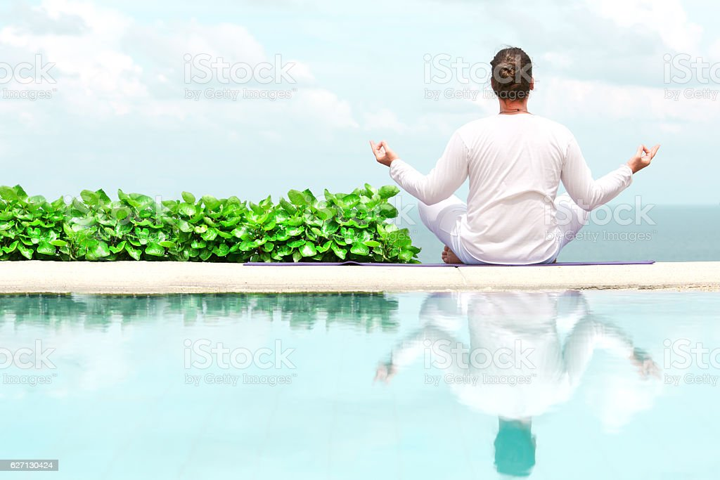 Man in white clothes meditating yoga on the sea shore stock photo