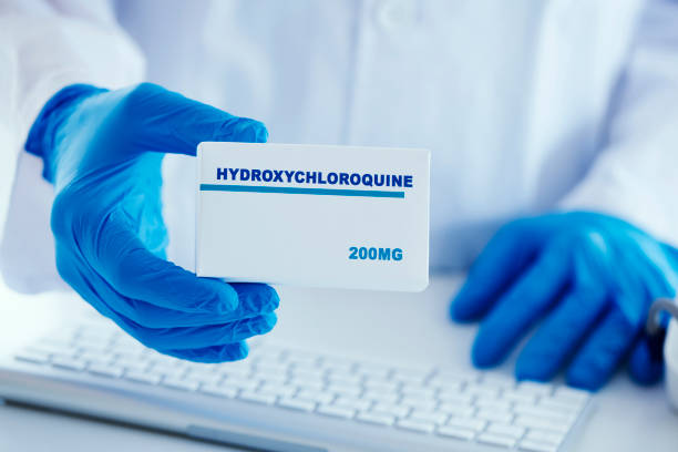 man in white coat with a box of hydroxychloroquine stock photo