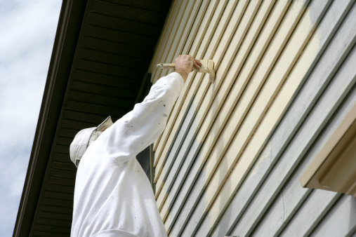 Man In White Coveralls Painting The Outside Of A House Stock Photo - Download Image Now
