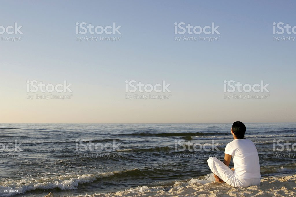 A man in white doing yoga on the beach royalty-free stock photo