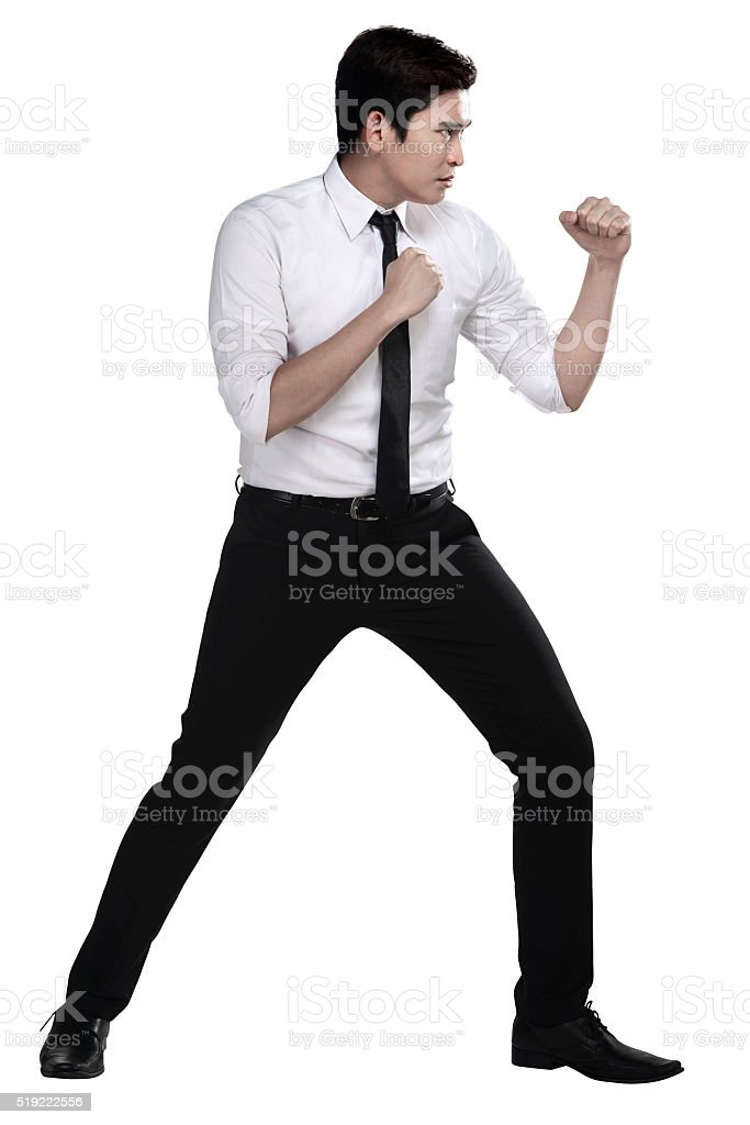 Man in white shirt doing fighting stance stock photo