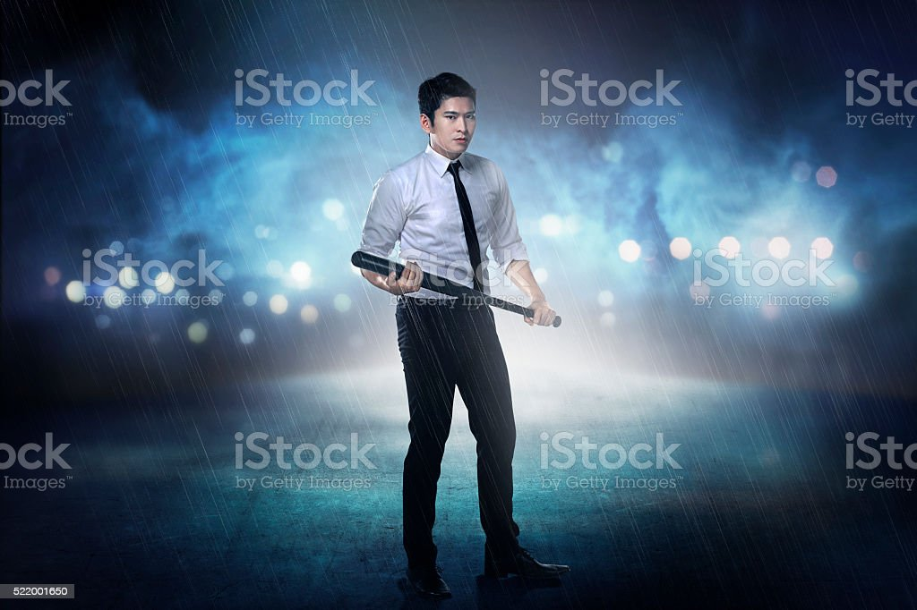 Man in white shirt holding baseball bat stock photo