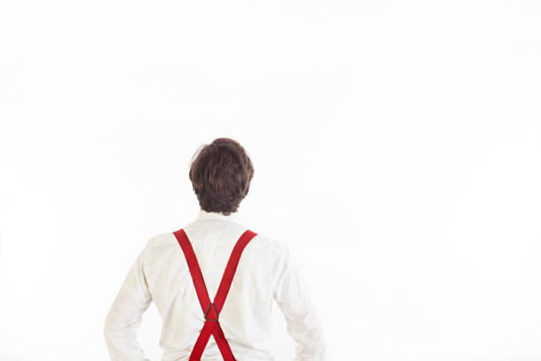 Man In White Shirt Looking Up with White Backdrop A man in a white shirt and red suspenders has his back to the camera and is looking up towards the floor, in front of a white backdrop with lots of space. suspenders stock pictures, royalty-free photos & images