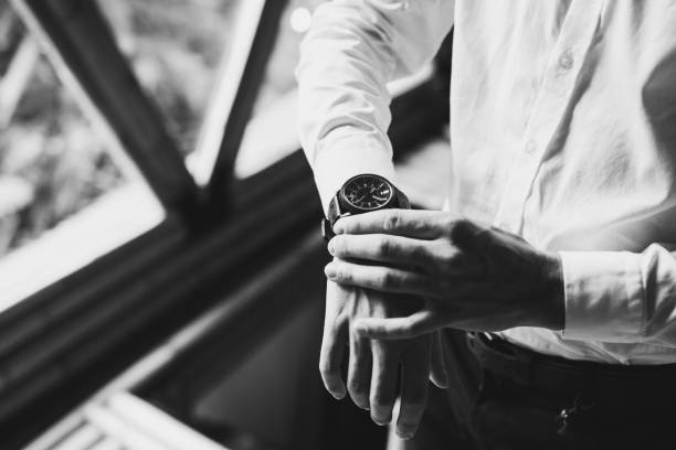 Man in white shirt wearing black watches. Black and white style photo Man in white shirt wearing black watches. Black and white style photo luxury watch stock pictures, royalty-free photos & images