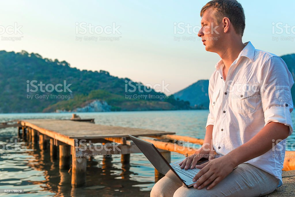 man in white shirt with laptop on the pier stock photo
