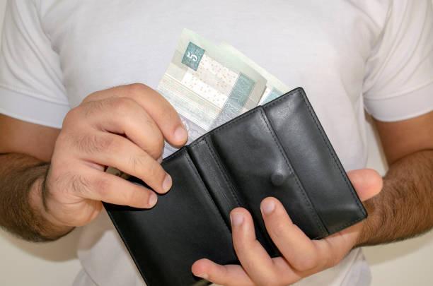 Man in white t shirt put egyptian pound banknotes into black wallet. stock photo