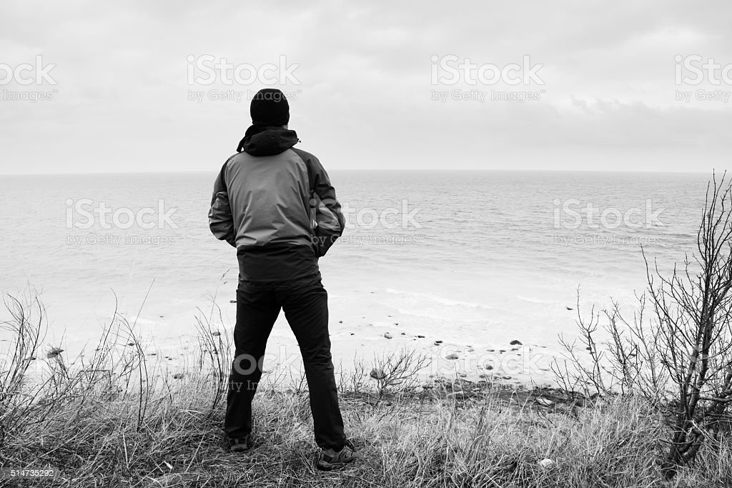 Man in windcheater on cliff above bay and see horizon stock photo