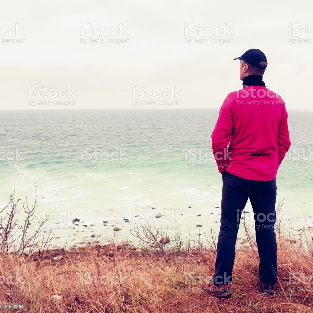 Man in windcheater stand on cliff above bay stock photo