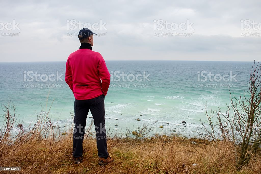 Man in windcheater stand on cliff above  sea. Windy weather stock photo