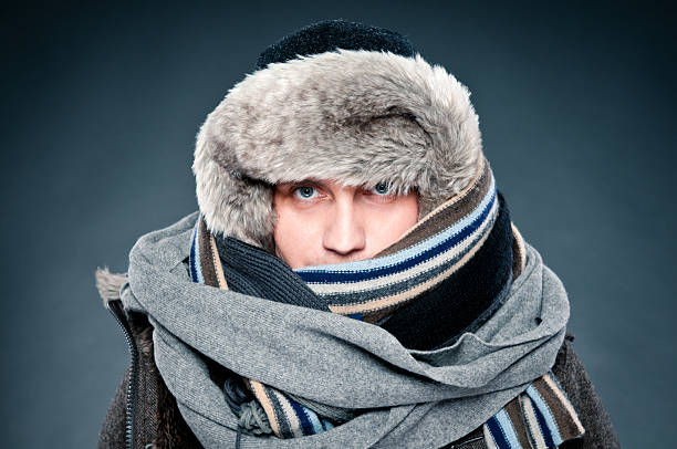 Man in winter clothes is tightly bundled up, cap, scarves Handsome man in winter clothes, very warm and thickly clothed. He has two scarves, thick warm fur cap. warm clothing stock pictures, royalty-free photos & images