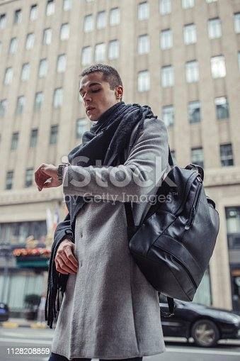 Fashionable handsome man wearing gray coat, long, black scarf and black backpack and checking the time.