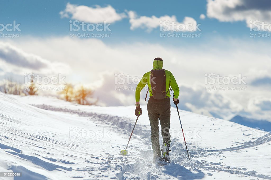 Man in winter landscape with snowshoes stock photo